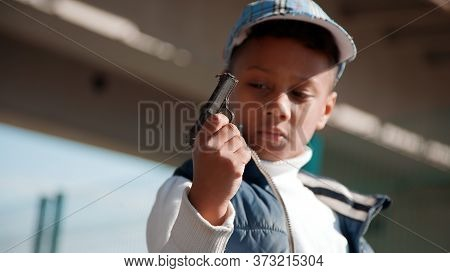 Black (african-american) Kid Playing The Gangster With Toy Gun (pistol) In City Street.