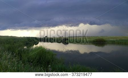 Thunderstorm Over The River. Low Clouds Before The Rain. A Thunderstorm And A Hurricane Are Approach
