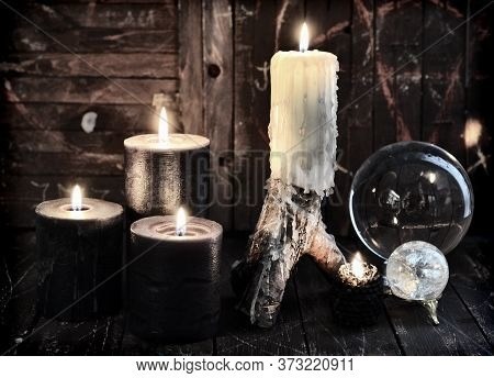 Burning Candles And Divination Crystal Ball On Witch Table. Esoteric, Wicca And Occult Background Wi