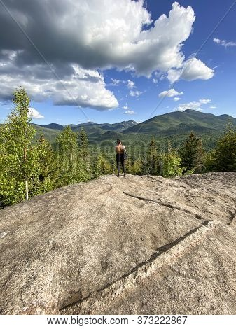 Woman At The Top Of A Mountain On A Hike, Taking A Photo Of The Beautiful Landscape During Summer