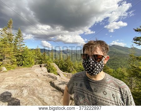 Man In A Mask Hiking On A Mount Top In The Adirondacks With A Face Mask.  Exploring Nature During Co