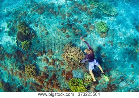 Happy Family Vacation. Man In Snorkeling Mask With Camera Dive Underwater With Tropical Fishes In Co