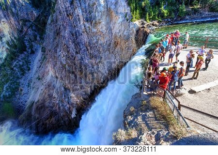 Wyoming, Usa - Aug. 27, 2019: Visitors Stand At The Brink Of Lower Falls At Yellowstone National Par