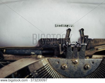 Loading Text Typed On White Paper In Vintage Background. Stock Photo.