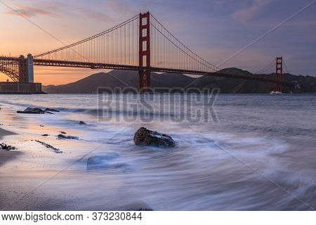 Long Exposure Of A Stunning Sunset At The Beach By The Famous Golden Gate Bridge In San Francisco, C