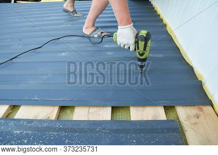 A Building Constructor Is Installing Lightweight Metal Roofing Sheet Using An Electric Screw Driver