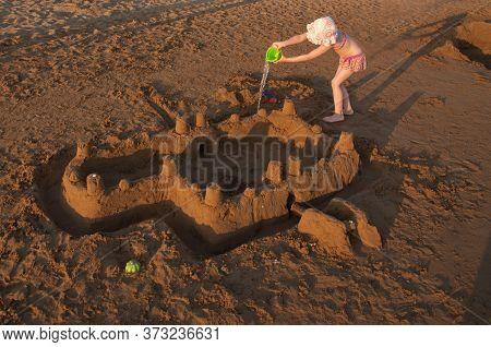 Little Girl Buiding Big Sandcastle On A Sandy Beach. Summer Vacation Concept
