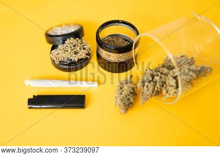 The Pot Leaves On Buds. Yellow Background. Thc Cbd. Cannabis Weed Bud And Grinder. Joint Weed.