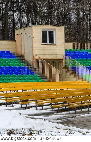 Spectator Seats In The Snow In Winter. Empty Seats Of An Amphitheater In A Winter Park.