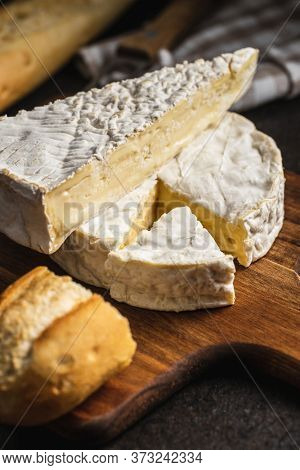 Brie cheese. White soft cheese with white mold on cutting board.