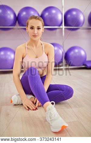 Sporty young girl in sportswear sitting on the floor and resting after training in the fitness center. Wellness. Fitness training.