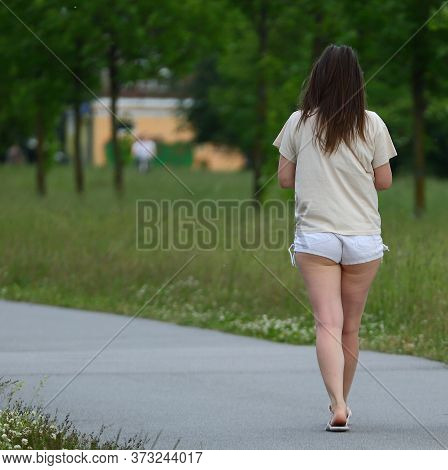 A Girl In Short White Shorts Walks Along A Park Path, Ulitsa Podvoyskogo, Saint Petersburg, Russia J