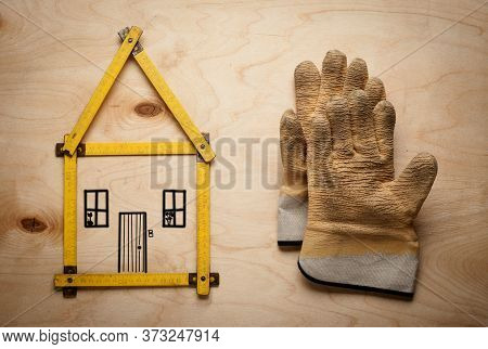 House Concept With Yellow Meter And Working Gloves On Wooden