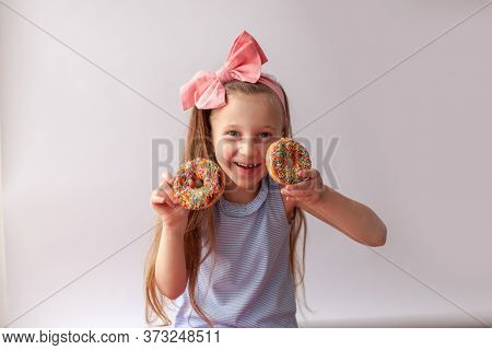 Happy Little 7 Years Girl With Classic Chocolate Donuts With Colorful Sprinkles In Her Hands.