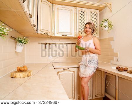 Sexy Blonde Housewife In Short Shorts With Tattoos At The Kitchen  With Tomatoes And Cucumbers. Diet