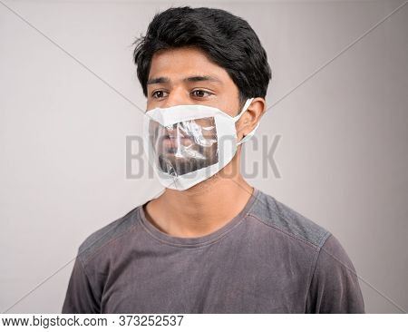 Young Man With Transparent Medical Face Mask, To Help Hearing Imperimeant Or Deaf People To Understa