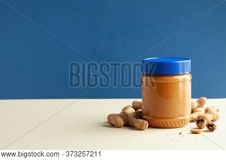 Closed Jar Of Peanut Butter, Peanuts In Their Shells. American Culture. Breakfast, Dessert For Veget