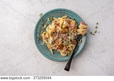Top View Pasta Fettuccine With Mushrooms, Bacon And Parmesan Cheese In White Plate On A Light Wooden