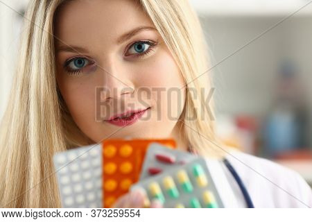 Close Up Of Attractive Young Woman Holding Different Medicaments And Smiling