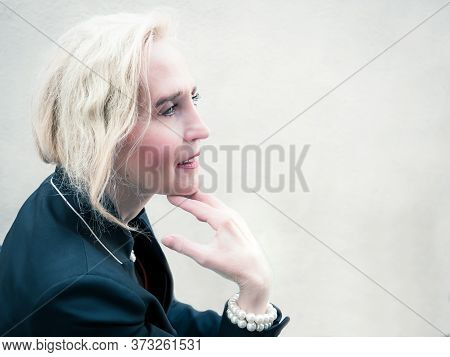 Horizontal Portrait Of A Classy Mature Woman Holding Her Chin With Her Hand