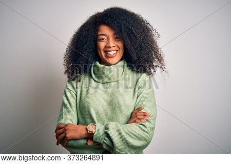 Young beautiful african american woman with afro hair wearing green winter sweater happy face smiling with crossed arms looking at the camera. Positive person.