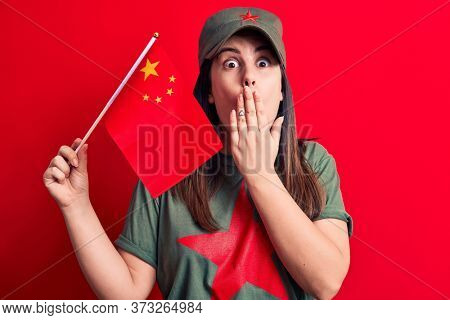 Beautiful patriotic woman wearing t-shirt with red star communist symbol holding china flag covering mouth with hand, shocked and afraid for mistake. Surprised expression