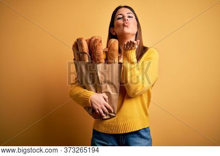 Young beautiful woman holding a bag of fresh healthy bread over yellow background looking at the camera blowing a kiss with hand on air being lovely and sexy. Love expression.