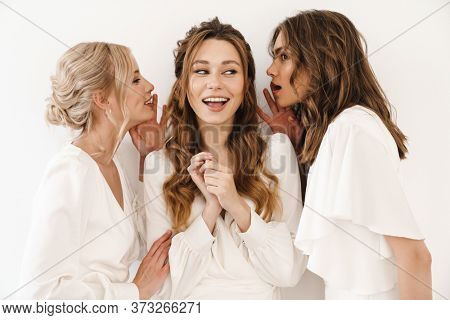 Photo of cheerful charming three women whispering and smiling isolated over white wall