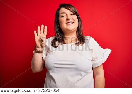 Beautiful brunette plus size woman wearing casual t-shirt over isolated red background showing and pointing up with fingers number four while smiling confident and happy.