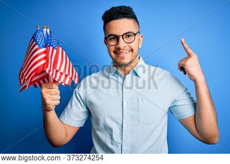 Young handsome patriotic man holding united states flags celebrating independence day surprised with an idea or question pointing finger with happy face, number one
