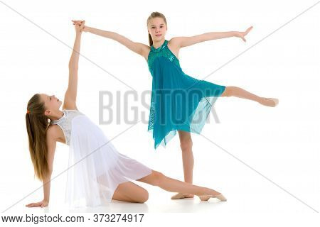 Two Pretty Gymnasts Performing Rhythmic Gymnastics Exercise, Portrait Of Beautiful Teen Twin Sisters