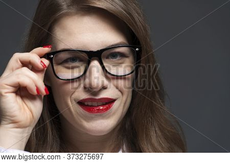 Close-up Portrait Of Young Woman With Eyeglasses And Red Lips Posing Over Grey Background. Eyeglasse