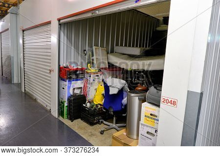 Indoor Storage Unit With Open Door And Household Goods In A Self Storage Facility. Rental Storage Un