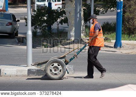 Worker In An Orange Vest Does Work On The Street.24.06.2020 Tashkent, Uzbekistan