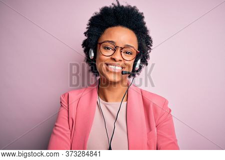 Young African American call center operator woman with curly hair using headset happy face smiling with crossed arms looking at the camera. Positive person.