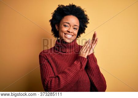 Young beautiful African American afro woman with curly hair wearing casual turtleneck sweater clapping and applauding happy and joyful, smiling proud hands together