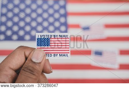 Holding I Voted My Mail Sticker In Hands With Us Flag As Background - Concept Of Voted Through Mail