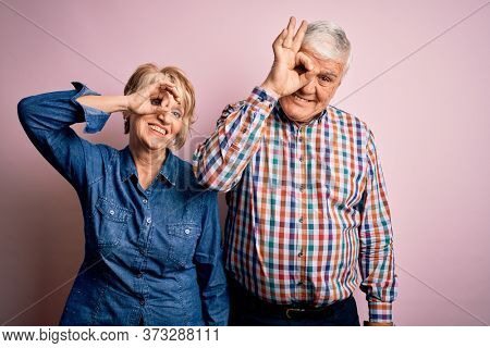 Senior beautiful couple standing together over isolated pink background doing ok gesture with hand smiling, eye looking through fingers with happy face.