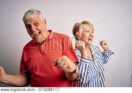Senior beautiful couple standing together over isolated white background Dancing happy and cheerful, smiling moving casual and confident listening to music