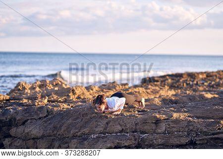 Young beautiful sportwoman practicing yoga. Coach teaching upward-facing dog pose at the beach