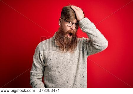 Handsome Irish redhead man with beard wearing casual sweater and glasses over red background surprised with hand on head for mistake, remember error. Forgot, bad memory concept.