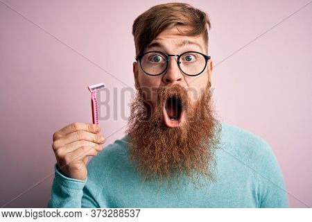 Redhead Irish man with beard holding beauty razor for shaving and skin care over pink background scared in shock with a surprise face, afraid and excited with fear expression