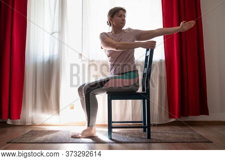 Woman Working Out Doing Yoga Or Pilates Exercise Using Chair.