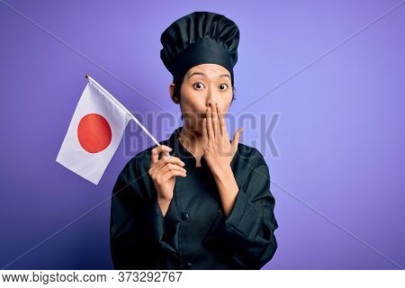 Young chinese chef woman wearing cooker uniform and hat holding japan japanese flag cover mouth with hand shocked with shame for mistake, expression of fear, scared in silence, secret concept