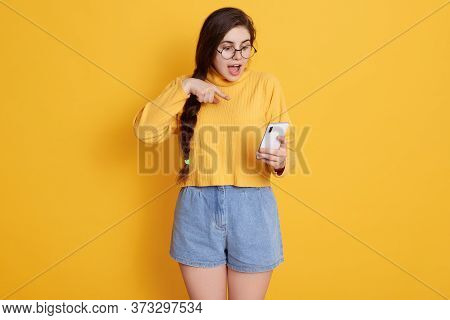 Lady With Opened Mouth Pointing At Smart Phone's Screen Which Holding In Hand, Female Wearing Sweate