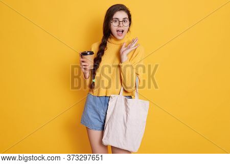 Astonished Buyer With Long Pigtail Holding Takeaway Coffee And Shopping Bag In Hands, Keeps Mouth Op