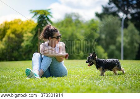 Young Woman With Beautiful Yorkshire Posing And Playing Sympathetically In A Garden With Grass And T