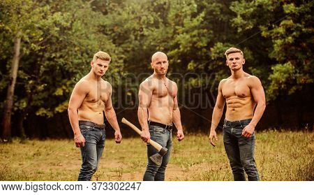 Full Concentration. Handsome Guys With Sexy Body. Sports And Leisure. Three Muscular Men With Axe. A