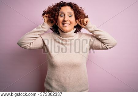 Middle age beautiful curly hair woman wearing casual turtleneck sweater over pink background Smiling pulling ears with fingers, funny gesture. Audition problem