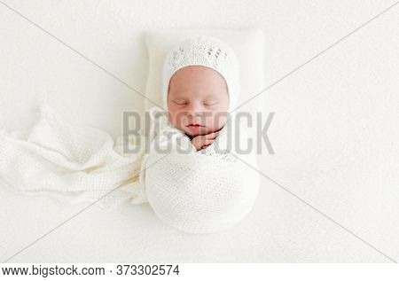Sleeping newborn baby girl wrapped in white blanket